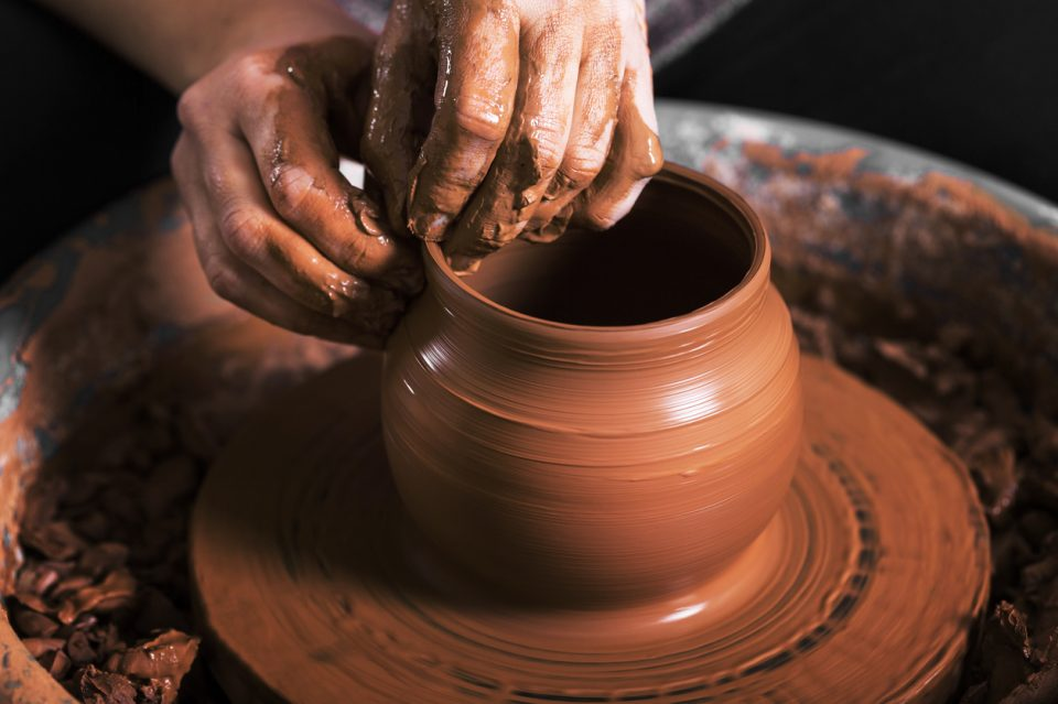 hands of a potter creating a jar in an art gallery