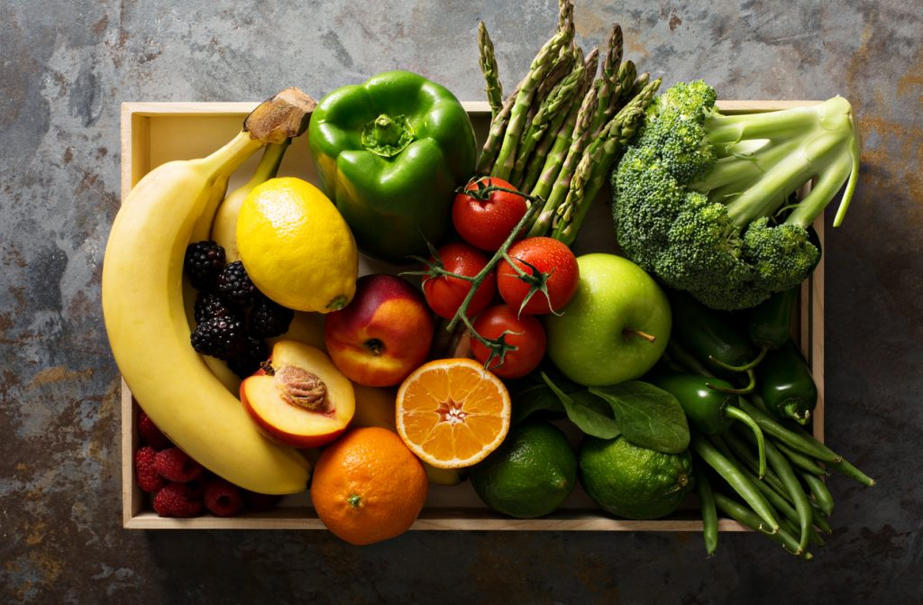 Fresh colorful summer fruits and vegetables in a crate