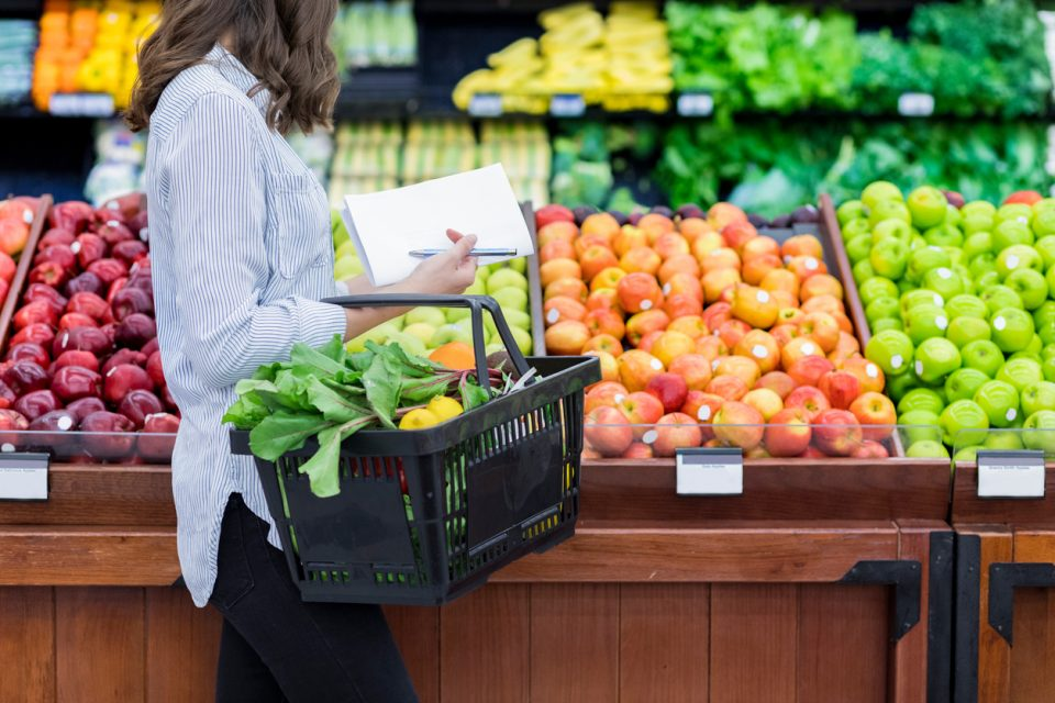 woman shops for summer fruits and veggies in supermarket