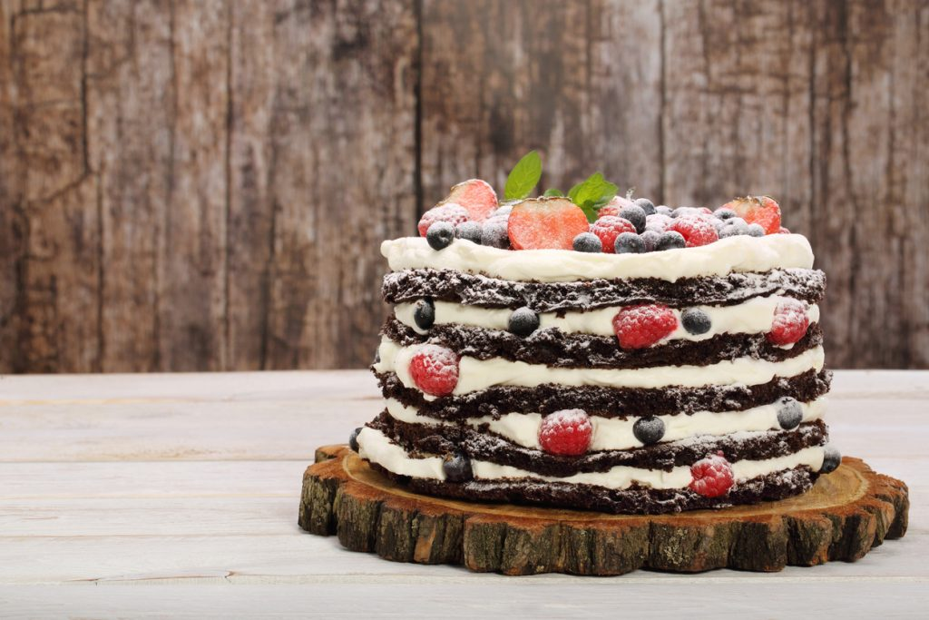Chocolate cake with white cream and fresh fruit at a bakery